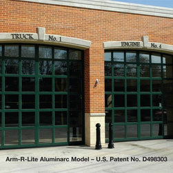 Arm-R-Lite Aluminarc Model Overhead Sectional Garage Door - Arm-R-Lite's Aluminarc overhead sectional roll-up aluminum and glass garage door in a custom green finish with specially designed arched design to accomodate this fire station's openings - Edison, NJ