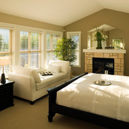 Blinds & Shades - White and taupe bedroom with fireplace and white faux wood blinds inside mounted in many windows with white trim.