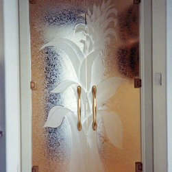 "Bromeliad Glass Doors - Bromeliad Glass Doors.... First impressions count!   ..... Glass Doors and Entries that Make a Statement.  Let Sans Soucie Art Glass transform the ordinary into the extraordinary with one of their signature frameless, all glass doors!  Glass front entry doors will be 1/2"" thick, while Interior glass doors can be 3/8"" or 1/2"" depending on the size, location and application.  Available any size, custom made to order, all glass is tempered for safety.   Interior glass doors will include wall mount hinges and solid metal door pulls.  Glass front entry or exterior doors will include top and bottom metal rails or patch fittings, header with concealed hydraulic closures, vertical jambs, lock box, threshold, back-to-back door pulls, all hardware (in a variety of finishes) and weather stripping and mohair door seals.   While any effect is possible on these doors, the majority of our clients who select frameless glass doors opt for the 3D carved option where the design is sculpted and will have a relief texture of varying depths. Glass is hand-crafted, sandblast frosted and 3D carved, art glass doors by Sans Soucie add a truly unique element and level of luxury, while providing privacy AND light!   From a little to a lot, the privacy you need is created without sacrificing sunlight.     From simple frosted glass effects to our more extravagant 3D sculpture carving, painted glass .. and everything in between, Sans Soucie designs are sandblasted different ways which create not only different effects but different levels in price.  The ""same design, done different"" - with no limit to design -  there's something for every decor, regardless of style.  Price will vary by design complexity and type of effect:  Specialty Glass and Frosted Glass.  For complete descriptions of glass types and effects, click here. Available any size, custom made to order and shipping worldwide at reasonable prices,   The sandblast artist literally cuts deep into the glass, using sand as their sculpting tool.  The edges of the carving illuminate bright as they pick up and reflect the surrounding light.   If color is desired, the 3D carved glass is airbrush painted in either translucent or solid paints, from matte to metallic.   Sans Soucie has hundreds of glass door designs available from simple to extravagant, and we specialize in creating new, custom designs specifically designed for your front entry."