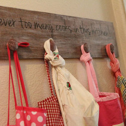 "Products - This hand painted wood apron hanger is the perfect pit stop for those cute aprons that have been stashed away in a drawer.  It has a cute saying on it, ""Never too many cooks in this kitchen!""  If you'd like something else, please inquire.  It also has 4 knobs for hanging."