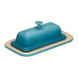 Le Creuset Butter Dish - Caribbean - Your food-savvy friends will fall in love with your Le Creuset Butter Dish - Caribbean. This little beauty has a gorgeous Caribbean blue enamel that's a snap to clean, durable enough for daily use, and resists chips, stains, and cracks. They'll know it's a Le Creuset by the signature 3-ring accent and smart handle. Not just pretty, this dish is crafted of stoneware so it retains cooler temperatures longer, leaving your butter spreadable, even when it's warm. It goes from fridge to microwave to dishwasher beautifully and even has a 5-year manufacturer's warranty.About Le Creuset of America Inc.From its cast iron cookware to its teakettles and mugs, Le Creuset is a global standard of inimitable color and quality. Founded in 1925 in the northern French town of Fresnoy-Le-Grand, Le Creuset still produces enameled cast iron in its original foundry. Its signature color, Flame, was modeled after the intense orange hue of molten cast iron within a cauldron (or Creuset in French), and has been a Le Creuset bestseller from the company's first year to the present day.Though best known for its vibrantly colored cookware and original inventions such as the Dutch oven, Le Creuset has also forged a name as a creator of stoneware mugs and enamel-coated stainless steel teakettles. The style and performance of Le Creuset's Cafe Collection and tea accessories are rooted in classic French cookware: bold colors, cylindrical loop handles, unmatched thermal resistance and heat distribution, and of course the iconic Le Creuset three-ring accent. Through its consistent qualities of authenticity, originality, and innovation, Le Creuset maintains a connection to both heritage and modernity.