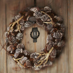 Faux Antler Wreath - Start on the outside of your house by adding a subtle wreath full of faux antlers and fall pinecones.