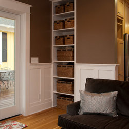 Custom Woodwork - In this family room addition we utilized space by custom building storage shelving.  York also custom built the wainscot and trim to match existing trim in the home.  Photography by Dane Gregory Myer Photography.
