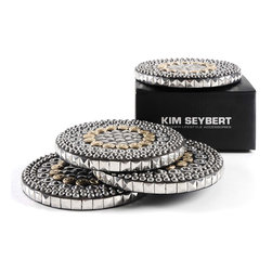 Heavy Metal Coaster - Set of Four - Casual, darkly glamorous transitional coasters bring a rockstar edge to your bar or coffee table with a mosaic of mixed metals edged in reflective silver studs. The metallic hardware that details the round coasters fills an elegantly aged palette of gunmetal black, bright silver, and dark antiqued gold. Incredible when glittering under glasses or mugs, the coasters strike a perfect balance between the airiness of a mirrored salon and the handsomeness of a shadowy den. This item is sold as a set of four.