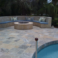 """Large Fire Pit - Custom half-round coral stone seat with cushions to match radius around 36"""" gas fired pit enclosed in 5' Dia. coral stone table."""