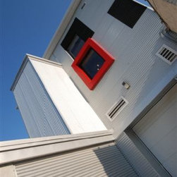 London Clay and Art Centre - In contrast to the Front Elevation - the Rear Elevation of the LCAC is a contemporary jewel, where the designer had creative freedom to apply punch-colours, box bays and corrugated metal siding along with the Tilt Turn Windows - shown here in black