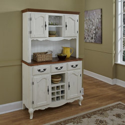Home Styles - Home Styles The French Countryside Oak and Rubbed White China Cabinet - 5518-617 - Shop for China from Hayneedle.com! Your Home Styles The French Countryside Oak and Rubbed White China Cabinet is an updated take on a traditional European farmhouse design. Perfect in the kitchen or dining room this china cabinet is made of hardwood solids and engineered wood with a hand-rubbed white finish. The top of the buffet and hutch are both crowned by distressed oak finished tops. Detailed brass hardware corner peg accents and cabriole legs enhance the look. The buffet features three drawers two cabinet doors with adjustable shelving a fixed middle shelf and removable wine caddy. The hutch adds two additional doors adjustable shelving and a bead board backing for added Provencal style. About Home StylesHome Styles is a manufacturer and distributor of RTA (ready to assemble) furniture perfectly suited to today's lifestyles. Blending attractive design with modern functionality their furniture collections span many styles from timeless traditional to cutting-edge contemporary. The great difference between Home Styles and many other RTA furniture manufacturers is that Home Styles pieces feature hardwood construction and quality hardware that stand up to years of use. When shopping for convenient durable items for the home look to Home Styles. You'll appreciate the value.