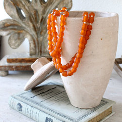 Small Orange Sea Glass Beads - A loop of medium sized frosty sea-glass beads in a delightful shade of orange, their texture pitted and clouded by wind and waves, fill a knotted strand of natural fiber to make a decorative necklace that looks great draped over a vintage box of treasures, arranged around a pillar candle, or hanging on a shapely vase. This simple designer trick brings a casual, summery feel to a room without the necessity of changing out furniture or other favorite ornaments with the seasons