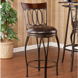 """Wildon Home � - Yorkshire Swivel Stool - Enhance your home with fashionable convenience. The cast ovals and curved legs of this stool create a sleek and sophisticated look. A powder-coated, dark champagne finish and durable steel frame deliver lasting quality. It features height seating, a cozy foam seat covered in rich dark brown vinyl, and a backrest accent in a rich walnut finish bentwood. A full 360 degree swivel and footrest ring provide comfort and ease. The curvaceous form and attractive finish coordinate with traditional to contemporary décor styles. Ideal for the kitchen, breakfast nook, bar, or dining area. The handcrafted touch of artisan skill also creates variations in color and design; slight differences should be expected. Features: -Champagne brown finish frame with rich walnut finish backrest and dark brown seat cushion. -Constructed of powder-coated steel, bentwood, vinyl, particle board, and polyurethane foam. -Sturdy steel frame with luxurious vinyl seat and fire-retardant foam cushion. -Smooth 360 degree swivel. -Convenient footrest ring for ultimate comfort. -Curved backrest for optimum support. Dimensions: -Backrest: 15"""" H x 15.75"""" W. -Cushions thickness: 3"""". -25-in. Seat: 25"""" H x 15"""" Dia.. -25-in. Footrest height: 6.5"""". -30-in. Seat: 30"""" H x 15"""" Dia.. -30-in. Footrest height: 11.5"""". -25-in. Overall: 37"""" H x 15.75"""" W x 18.5"""" D, 20 lbs. -30-in. Overall: 42.25"""" H x 16"""" W x 18"""" D, 21 lbs. -Max weight capacity: 250 lbs."""