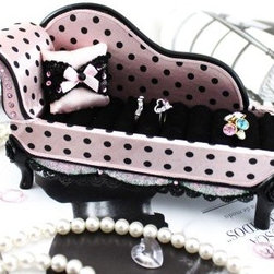 Polka Dot Romance Lounge Chair Ring Holder - Retro glam right on your vanity top, the Polka Dot Romance Lounge Chair Ring Holder is a cute mini lounger loaded with details and color. It comes in black, hot pink, light pink, or purple and is accented with lots of sparkly details. Your rings are shown off in style on the matching ring roll topper and it even includes a mini pillow with lace, bow, and faux crystal details. A handsome box makes this beauty ready to gift.About Jacki Design InternationalBased in Los Angeles, Jacki Designs imports gifts, jewelry, displays, train cases, cosmetic bags, and accessories. They take pride in keeping up with very latest trends and offer superior quality, affordable items perfect for today's homes. Whether you're shopping for wedding accessories or gifts, Jacki Designs has something for you. You'll love the vibrant colors, sparkles, and smart design on all their products.