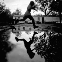 OAC Gallery - Leap - Limited Edition Photography by Brandon Thibodeaux - A young boy leaps over a water puddle after a summer rain at his home in Duncan, Mississippi. This is from a series called, When Morning Comes, which is a reflection of life in the Mississippi Delta.
