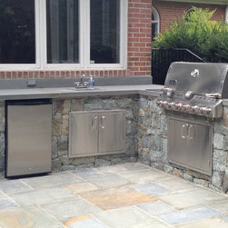 Outdoor kitchen - Some homeowners prefer a full kitchen layout for outdoor grilling. This L-shaped space provides ample space for a full sink, large grill, storage cabinets, and stainless steel trash drawers. A durable stone countertop and stone veneer makes it feel like it has always been there.