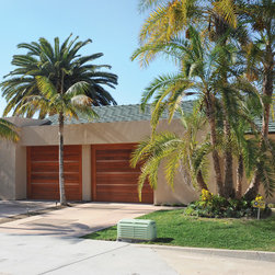 La Jolla Custom Wood Garage Doors - Here we helped the homeowner to design African Mahogany doors with a Copper Accent Strip.  The design was chosen to allow the garage doors and gate to complement each other.