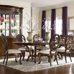 """American Drew Jessica McClintock Couture 7 pc. Dining Table Set with Splat Back - Friends and family will enjoy a refined elegance when dining around the American Drew Jessica McClintock Couture 7 pc. Dining Table Set with Splat Back Chairs. Crafted from solid hardwoods and maple veneers and given a walnut finish. This set comes with our beautifully detailed splat back chairs and oval table with extension leaf. This table features intricate wood grain detailing and seats 6 comfortably. Each chair is adorned with a patterned cream upholstery. This set is ornate enough for formal dining and toned enough for casual dining. The contrasting dark wood with the cream upholstery adds so much beauty to this set. Delicate carved chair backs are defined style. Chair legs have curved backs with scrolling fronts that match the scrolled table legs. Table dimensions: 82-134L x 49W x 30H inches. Chair dimensions: 22W x 27D x 42H inches. Choose to add the matching Jessica McClintock Couture China Cabinet to complete the look of your room. Adds beautiful storage and display. Features include: Solid hardwood and maple veneeer construction with walnut finish. Mirrored back with interior lighting. Glass front doors and shelves. 2 doors in base with adjustable shelf interior. Ornate scroll designs at each corner. Hutch has glass display on 3 sides. China cabinet dimensions: 77W x 25D x 88H inches. About American DrewFounded in 1927 American Drew is a well-established leading manufacturer of medium- to upper-medium-priced bedroom dining room and occasional furniture. American Drew's product collections cover a broad variety of style categories including traditional transitional and contemporary. Their collections range from the legendary 18th-century traditional """"""""Cherry Grove """""""" celebrating its 42nd year of success to the extremely popular """"""""Bob Mackie Home Collection """""""" influenced by the world-renowned fashion designer Bob Mackie. """"""""Jessica McClintock Home"""""""" features another beloved des"""