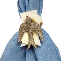 Sparkle Dove Napkin Rings - Set of 4 - A surprising touch of softness backs an updated motif in classic dress. The Sparkle Dove Napkin Rings place glimmering metallic birds, sculpted in mid-swoop, on a bed of carefully-folded ivory grosgrain ribbon, drawing on the style of a wrapped gift to give your tabletop a festive look that especially suits the New Year but looks lovely in all seasons.