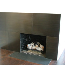 fire place - With these brushed bronze panels this fire place is the center of attention.