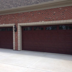 Traditional Raised Panel Garage Doors - This photograph is a wonderful display of the garage door with a Classic Cherry Wood Grain  tying in the red from the brick.  What a great look!