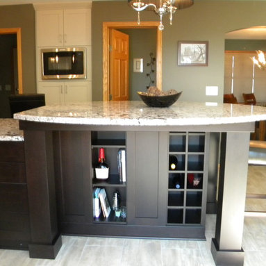 Midwestern Mod - Raised table section houses, built in wine cubbies, and cookbookshelves on both sides, also serves a functional support to the large oval shaped raised granite table top