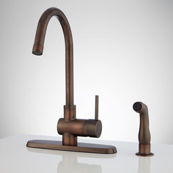 Healey Kitchen Faucet with Side Spray - Sporting a tall gooseneck design and cylindrical accents, the Healy Kitchen Faucet lends a modern look to your kitchen sink. A single-lever handle lets you adjust water temperature with ease and a side spray allows you to reach all areas of your sink and beyond. This minimalist fixture is made of brass and includes a deck plate.