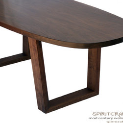 "The Mod Century Oval Dining Table in Walnut - A Spiritcraft Design original, this oval dining table measures 96"" long by 36"" wide. The design features slab mitered and splined legs and a solid hardwood book-matched slab top."