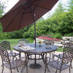 Oakland Living - 8-Pc Outdoor Dining Table Set - Includes dining table, six stackable dining chairs and 9 ft. tilting umbrella with stand. Crisp and stylish traditional lattice pattern and scroll work. Umbrella hole to table top. Center of table can be replaced with ice bucket. Metal hardware. Fade, chip and crack resistant. Warranty: One year limited. Made from rust free cast aluminum. Antique bronze hardened powder coat finish. Minimal assembly required. Chair: 23 in. W x 22 in. D x 35.5 in. H (25 lbs.). Table: 60 in. Dia. x 29 in. H (70 lbs.)The Oakland Mississippi Collection combines southern style and modern designs giving you rich addition to any outdoor setting. This dining set is the prefect piece for any outdoor dinner setting. Just the right size for any backyard or patio. We recommend that products be covered to protect them when not in use. To preserve the beauty and finish of the metal products, we recommend applying epoxy clear coat once year. However, because of the nature of iron it will eventually rust when exposed to the elements.