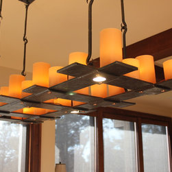 Grid Candle Chandelier - Lapped and riveted, heavy flat bar chandelier. Led lit candles and inset down lights. Forged hanging hooks.