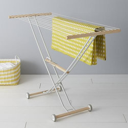 """Aris Drying Rack - Italian-designed collapsible drying rack hangs garments from coated nylon cords suspended on a durable aluminum frame with beechwood crossbars and accents and convenient wheels. Pull the convenient lift handle to quickly fold up the rack to a slim 10"""" storage profile."""