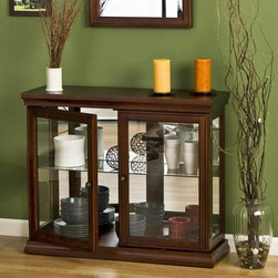 Holly & Martin - Arabella Double-Door Curio in Mahogany Finish - A console curio provides enclosed space for protecting collectibles along with an upper display area for everyday items.  Create a focal area with this rich mahogany design that's low enough to group with dramatic vases and floral arrangements, plus mirrors and art collections above. * Curio cabinets are a wonderful way to accent, display, and decorate your home and belongings. This curio is no exception with its exemplary styling and design. The rich mahogany finish really stands out as is accents the spacious interior.  Matching mirror not included. Interior Shelf is Adjustable. Interior is not lighted. Assembly: Required. Material of construction: Poplar / MDF / Glass. 36 in. W x 30 in. H x 12 in. D. Interior shelf: 10 in. Deep x 32 in. Wide