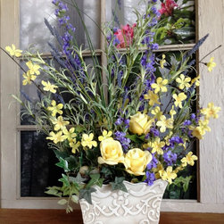 Floral Table Centerpieces - This elegant spring and summer floral table decoration arrangement is handcrafted with artificial purple delphiniums, yellow roses, lavender buds, miniature yellow flowers, greenery, and a grapevine birds nest with faux decorative eggs. The container is an antiqued embossed metal container in an off-white color.