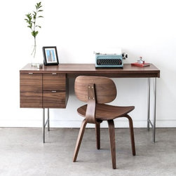 Gus Modern Conrad Desk - The Conrad Desk by Gus Modern is a compact home office desk with a strong Mid-Century pedigree. All surfaces are finished in walnut, to contrast the slender, tubular stainless steel legs and brushed aluminum drawer pulls. The main drawer is designed to hold hanging file folders, and the two smaller drawers are perfect for organizing stationary and supplies. This desk evokes the style of 1950s Modernism, but with a scale and functionality suited perfectly for today.