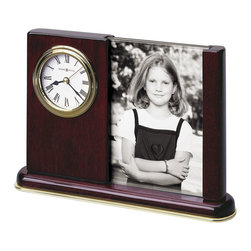 Howard Miller - Howard Miller Portrait Caddy Table Top Clock - Howard Miller - Mantel / Table Clocks - 645498 - This traditional portrait clock puts the time of day next to a special photograph of your choice. Distinguished by its polished gold waterfall bezel and classic dial and rosewood finish the Portrait Caddy is dual-sided for two photos and also features an attractive molded wood base. Battery-operated quartz movement ensures consistent timekeeping and rounds out the appeal of the Portrait Caddy Table Top Clock.
