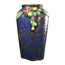 Pre-owned Large Italian Majolica Umbrella Stand Vase - Standing at nearly 19 inches high, this large Italian majolica umbrella stand jardiniere vase will be the star of your majolica collection! The hand-painted finish is blue and brushed gold, and the raised fruit surrounded by green leaves is literally cascading down the sides of this umbrella stand! Cherries, pears, pomegranates and grapes add visual interest with their pretty, hand-crafted details. You certainly could use this large majolica vase as a jardiniere or planter as it comes with a ceramic disc that is meant to allow water to drain when used as an umbrella stand. However, this beautiful vase would look just as lovely filled with dried flowers or foliage and sitting in a corner or entryway. Please note, there has been professional ceramic restoration to one of the fruits on the side of the vase which is barely visible.