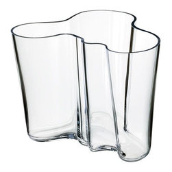 "iittala - Alvar Aalto Large Clear Vase - A shape constantly interpreted, the Alvar Aalto collection of vases stays true to the original design concept. More than 70 years after the original debut, the design continues to provoke attention by letting the owner decide its use and complementing our busy lives with a touch of nature. Filled with fresh cut flowers or arranged with other collection pieces as works of art, this eternal classic is essential to the modern home. The Aalto glass pieces have a multi-stage production. The non-leaded crystal is first mouth blown before going into a wooden mold to create the classic Aalto shape. The pieces are then hand cut and go through several polishing and finishing steps before they are completed, creating a piece worthy of permanent display at the Museum of Modern Art. In addition to the standard Aalto colors, each year iittala selects two new glass colors to run in limited production. Features: -Mouth blown non-leaded crystal -Features designer's signature on the bottom -Not dishwasher safe, hand wash only -Overall dimensions: 6.25"" H"