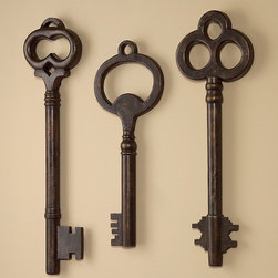 Whimsical Key Wall Art Sculptures - Set of 3 - The detailed teeth and shapely heads of this trio of dark bronze keys bring a hint of fun to your decor along with their distinguished artisan finish. An on-trend motif with a personality that fits into any decor theme, the skeleton key wall sculptures are perfect in a transitional entryway or hung above a handsome study desk. Slight variations in height allow for either a structured ordering or a more casual arrangement of the Whimsical Key Wall Art.