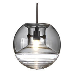 """Tom Dixon - Flask Smoke Pendant by Tom Dixon - Bottoms up! The Tom Dixon Flask Pendant is composed of two distinct segments of gorgeous handblown glass. The top portion is a Smoke glass """"hood"""" that serves to slightly obscure the inner hardware while also working to diffuse any glare issues. The internal ridges embedded within the bottom layer of cast waves of rippled ringed shadows as the light warmly filters through the textured glass base. Tom Dixon has a vast commitment to design creativity and a mission to redefine how products are made and sold. The Tom Dixon lighting and furniture collections reflect all of his cutting-edge design and manufacturing innovations, from the product's shape and form to the raw materials and production processes used."""