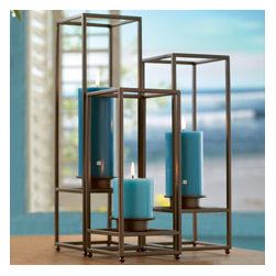 """Framework Collection - This trio brings glow out in the open! Group all three holders together for an impressive display. Metal frames feature a bronze finish for rustic charm. Includes three tall frosted glass cups for use with tealights and votives, or use without the cups and insert a pillar or Escential jar. All candles sold separately. One holder in each size: 18""""h, 15""""h, 12""""h; 5"""" square."""