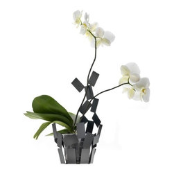 "Alessi - Stanza Scirocco Vase Cover in Black - The Stanza dello Scirocco, a project designed by Mario Trimarchi and presented in 2009 consisting of a small Basket, a tea light holder, a Fruit holder, a centerpiece, and a fruit bowl, has been enlarged to include a vase cover for orchid. Thanks to its light, airy form, this vase cover allows you to perceive a space of light and shadow between the container and its contents. This precious effect is cleverly obtained in a by inserting transparent floral water tubes, like the plastic ones normally used with orchids, into small vase covers. The part of the vase cover that extends upward holds the orchids' stems erect, thereby eliminating the unsightly supports normally used. Features: -Color: Black. -Material: Steel colored with epoxy resin. -Dimensions: 14"" H x 7.5"" W x 7"" D."