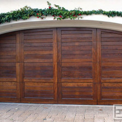 Dynamic Garage Door - California Dream 02 | Customi Wood Garage Door with a Subtle Mediterranean Flair - Horizontal Select Tongue and Groove Solid Cedar Boards and trim give this garage door an architectural statement that truly differentiates it from most semi-custom wood garage doors. It is so well-designed that the section cuts are nearly impossible to detect except when operating the garage door. This custom garage door design was made to stand alone without the need for accentuating iron decorations. Admire the beauty of the wood grain and subtle stain color a door like this will definitely improve or enhance your home. Dynamic Garage Door manufactures high quality architectural garage doors that can be installed within California and shipped throughout the state and abroad. Get a free estimate today and find out how your home's curb appeal can be dramatically enhanced with one of our garage doors.