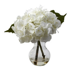 Blooming Hydrangea with Vase Arrangement - Large Hydrangeas have an almost cloud-like softness to them - you could almost imagine laying down in a bed of them and drifting off to dream world. And we've perfectly captured that feeling in this amazing reproduction. Gorgeous Hydrangeas stems, leaves, and a burst of softness that only the Hydrangea can offer. Comes complete with a glass vase and faux water. Height= 13 In. x Width= 10 In. x Depth= 10 In.