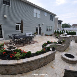 Travertine Pavers - Retaining Walls in Bohemia NY 11716 – Long Island - This photo we see a beautiful patio made of Bianco Anticato Pavers surrounded by retaining walls and columns made of the same pavers to accent the patio in Bohemia NY 11716. On the columns we see some outdoor lighting fixtures that make this family's backyard evening friendly. We also see a variety of garden ornaments such as a small water fountain that accents the patio in the flower bed. In the flower beds we see a variety of green and red landscaping, these two colors really pop against the beige and greys in the stones of the patio and retaining walls. We also see an outdoor kitchen and bar which are perfect for entertaining guests in the warm summer months.