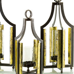 Table-Hanging Lantern Medium - Whether resting on a tabletop on its four ball feet, or hanging by its double ring from a ceiling or deck beam, this transitional candle lantern glimmers with metallic heat. The outer frame is composed of four flat, angled bars of natural iron forming a cage equipped with bright gold-leafed reflecting panels. In the center, a wavy glass hurricane chimney provides a protected place for a candle to burn, brilliantly lighting the surroundings.