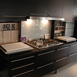 Cabinet details & specialty cabinets - A bank of contemporary kitchen cabinets, including backsplash cabinets with flip down glass fronts, customizable interiors showing spice shelves, knives divider and cutting boards.