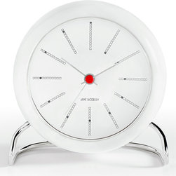 """Rosendahl - Banker's Alarm Clock - Rosendahl - After many years of being forgotten, the Arne Jacobsen relaunch has reintroduced the table clock into modern interior design. Thanks to updated functions such as snooze and light sensors, the table clock serves as both a clock and an effective alarm clock, but most will probably use the new table clock as a design object. With its graphic black/white color scale and elegant metal foot with unmistakable inspiration from """"the Ant"""" and """"Seven"""" chairs, the table clock fits in well anywhere in a modern home: in the bedroom, living room, kitchen, on shelves and not least in the office as the ultimate gadget for design lovers. Led light, white face, black markers, red center and alarm function."""