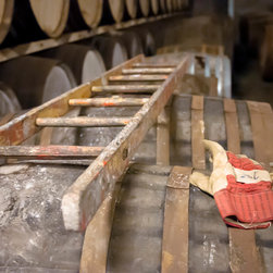 """Ladder and Glove, 16x16"""" fine art color photograph - Fine art photograph of a ladder and glove on whiskey barrels in the aging room at a Scotch distillery. Available as a 16x16"""" limited edition fine art photograph, printed archivally on photo rag paper. Unframed."""