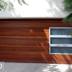 Modern Garage Door in a Horizontal Wood Slat Design w/ Accent Side Glass Panels - Located in Los Angeles, California this historic home from the 40's was retrofitted with a Mid Century / Modern style garage door with horizontal clear cedar wood slats and beautifully accentuated with side lite panels consisting of era-appropriate reeded glass and doubled up with frosted laminate glass for added security and privacy. Dynamic Garage Door introduced this type of design several years ago with other manufacturers following our design lead by simulating similar accents. As a true pioneer in garage door architectural design we are always evolving, cleaning up our designs and providing our clients with one-of-a-kind garage door designs that complement their home's architecture. The styles of the Mid Century are coming back and are highly acclaimed for their fine and minimalistic designs that evoke simplicity, function and modest beauty. We understand that as garage door design and manufacturing firm and as such we are able to create something entirely unique to your home without forcing you to settle for a garage door design that comes straight out of a cookie-cutter catalog.