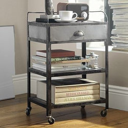 "Metal Rolling Cart Bedside Table - Our designer spotted a vintage metal cart at a flea market and replicated its weathered patina and durable design in this bedside table. Crafted from iron, the table features a convenient combination of open and closed storage, and a gallery rail around the top to keep items in place. 20"" wide x 14"" deep x 31"" high Crafted of welded high grade iron. Clear-coat finish on the shelves and drawer contrasts with the frame's darker patina. Gallery rail on three sides secures tabletop items. Roomy drawer and open shelving provide ample storage space. Casters provide easy mobility."