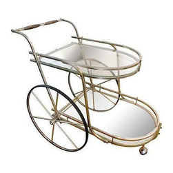 Used Hollywood Regency Bar Cart - A stylish Hollywood Regency bar cart featuring oversized wheels, curvaceous lines with a glass top and bottom serving trays. Store and serve your liquor in style or use it for tea and coffee. This is a unique accent piece with a brass toned metal frame. Cheers!