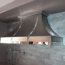 Hidden Hills, CA - This custom stainless steel range hood has a touch of traditional with contemporary materials. The hood has a non directional finish with polished stainless steel straps and brushed stainless steel rivets, along with a nice decorative crown molding trim at the stone ceiling.