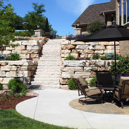 Natural Landscape Stone - Multi-tiered, natural stone retaining wall with snapped stone steps leading to patio.