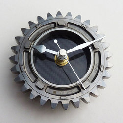 Get in Gear Wall Clock - Made from a 2007 Honda F1 4th gear ratio, this clock ups the steampunk style of any modern industrial home. High quality carbon fiber makes up the clock's center/face and each gear has been engraved by the Honda F1 team with a unique identification number.